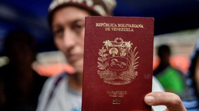 Una mujer venezolana muestra su pasaporte.