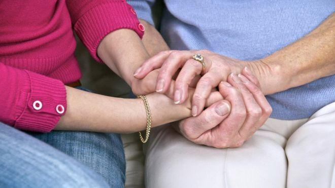 Пожилая и молодая женщина, держащая руки