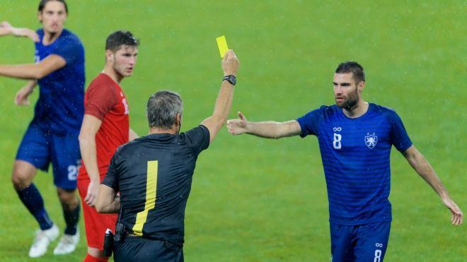 Juiz de futebol mostra um cartão amarelo para um jogador no campo
