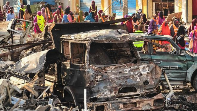 People gather near burnt vehicles a day after a truck bomb exploded in the centre of Mogadishu