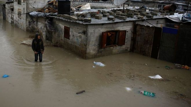 A man walks in a flooded area in northern Gaza, February 2017