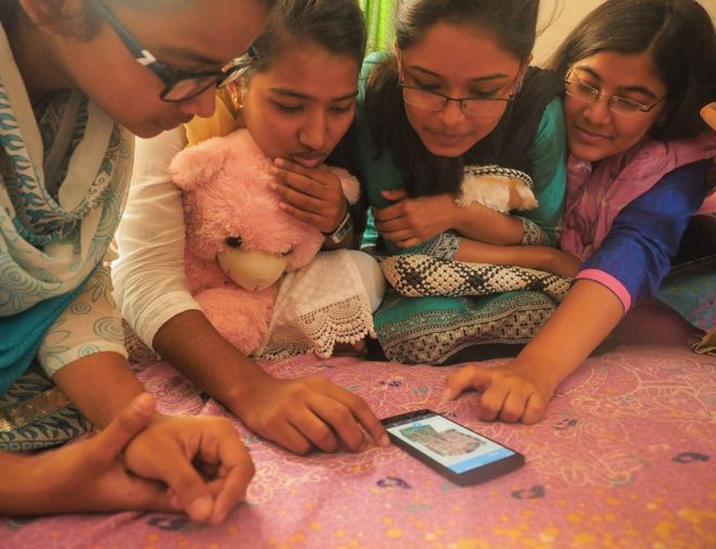 Bangladesh, 2015. Women gather around a smart phone.