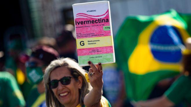 Una mujer en Brasil asiste a una manifestación de apoyo al presidente Jair Bolsonaro y sostiene una pancarta que imita una caja del fármaco ivermectina