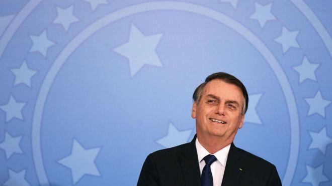 Bolsonaro sorri em frente a painel com brasão