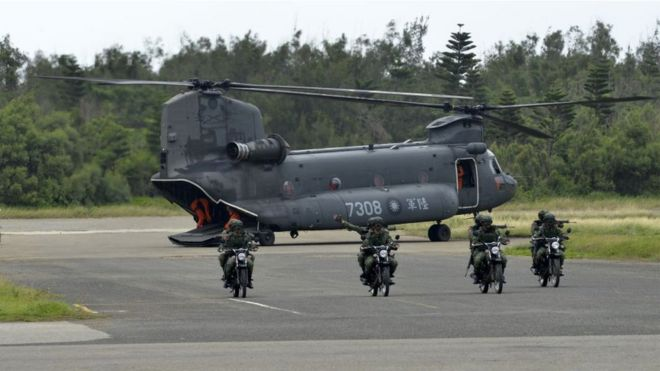 Armed Taiwanese soldiers ride on motorcycles next to a US-made CH-47 helicopter during the 'Han Kuang' (Han Glory) life-fire dril