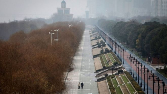 Two people walk down an empty street in Wuhan, 27 January 2020