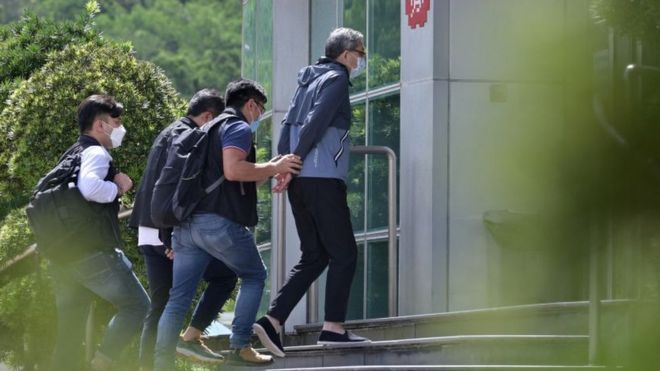 香港警方國安處便裝警員把壹傳媒行政總裁張劍虹(中)押入壹傳媒總部大樓(17/6/2021)
