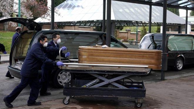 Les employés d'une morgue entrent dans le crématorium du cimetière de La Almudena avec un cercueil d'une personne qui est morte de la maladie coronavirus à Madrid, Mars 23, 2020