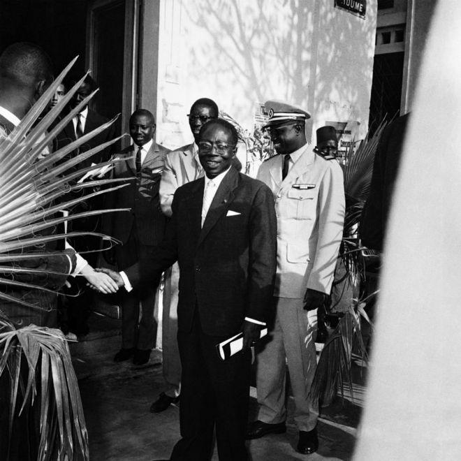 Des membres de la sécurité présidentielle entourent Léopold Sédar Senghor, alors président du Sénégal, qui serre la main d'un homme.