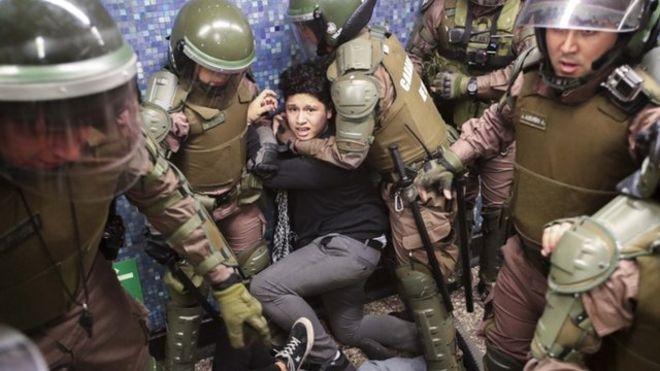 Varios agentes sujetan a un manifestante en el metro de Santiago