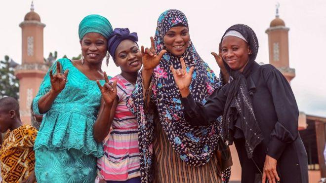 Au Ghana, des jeunes femmes portant des vêtements traditionnels posent pour une photo à l'occasion de l'Aïd.