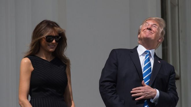 US President Donald Trump, with First Lady Melania Trump at his side, looks up at the partial solar eclipse from the balcony of the White House in Washington, DC, on August 21, 2017