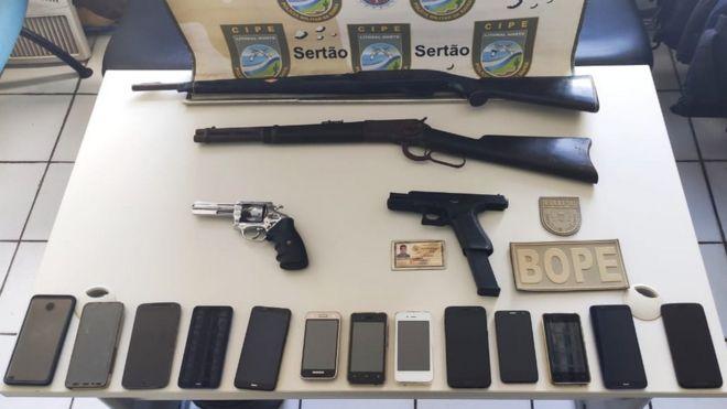 Polícia baiana exibe armas e celulares que diz ter encontrado onde Adriano Nóbrega estava escondido