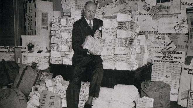 Postmaster General James Farley sentado em uma pilha de cartas (1938)