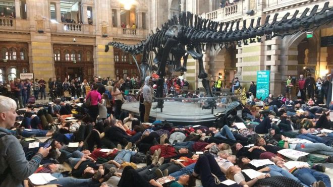 """Wee Rebellion protesters stage a """"die in"""" beneath Dippy the Dinosaur at Kelvingrove Art Gallery and Museum in Glasgow"""