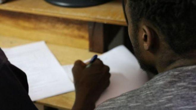 Foto ilustrativa de homem negro assinando documentos