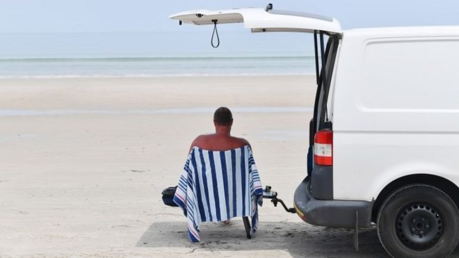 Man sits in the shade on a beach in Adelaide, Australia