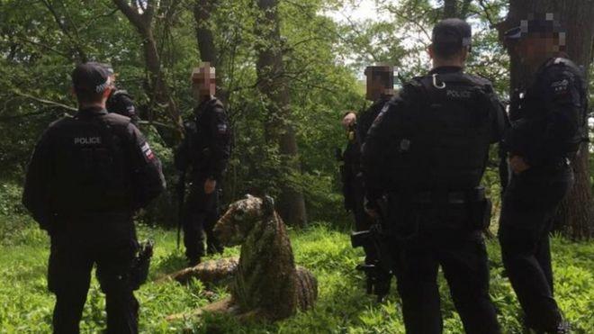 Скульптура тигра и вооруженные сотрудники полиции