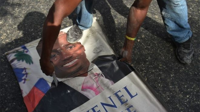 Protesters destroy a poster of Haitian President Jovenel Moise as they demonstrate in the Port-au-Prince suburb of Petion-Ville on July 7, 2018, against a hike in fuel prices.