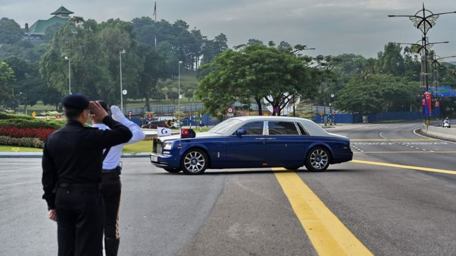 Policemen salute as a Rolls-Royce belonging to the Sultan of Johor enters the Istana Bukit Serene palace
