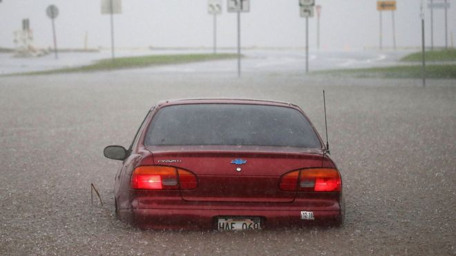 A car is stuck partially submerged in floodwaters from Hurricane Lane rainfall on the Big Island, Hawaii, 23 August 2018