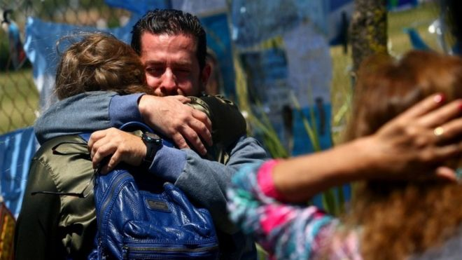 A crying man holds a woman in an embrace outside the Mar del Plata base on 25 November