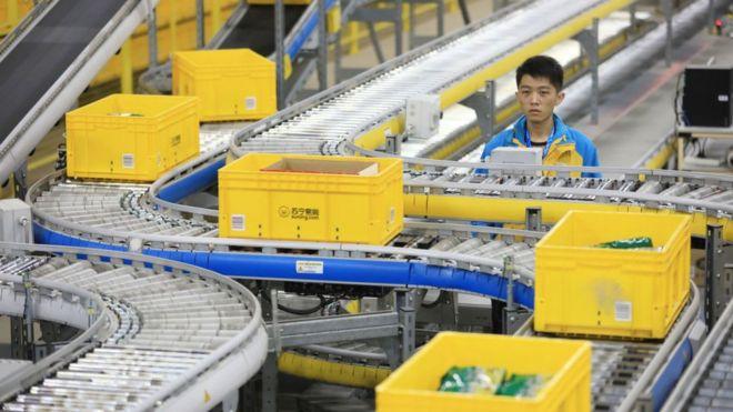 Man next to conveyor belt in Alibaba fulfilment centre.