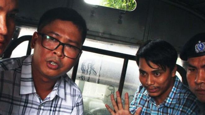 Wa Lone, left, and Kyaw Soe Oo gesture to the camera wearing handcuffs after their arrest in 2018