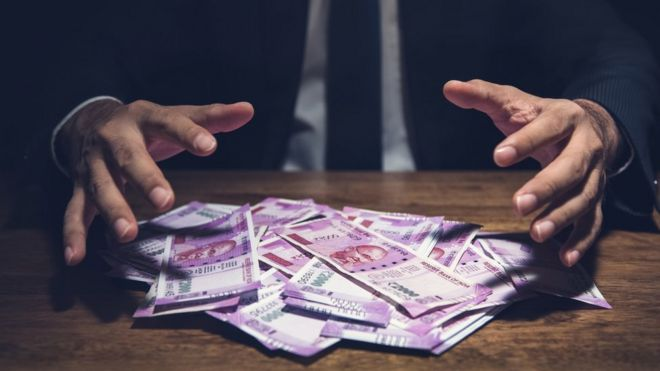 Businessman taking pile of money, Indian Rupee banknotes, on his desk in a dark office