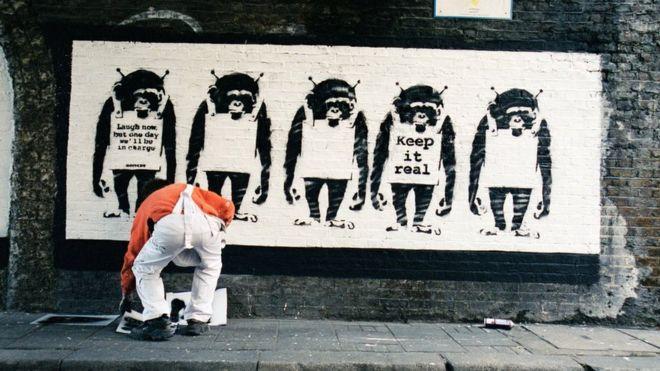 Artista ao lado de uma obra de Banksy