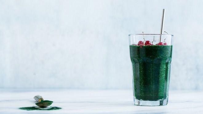Soothie de suco verde com spirulina ao lado de colher de spirulina
