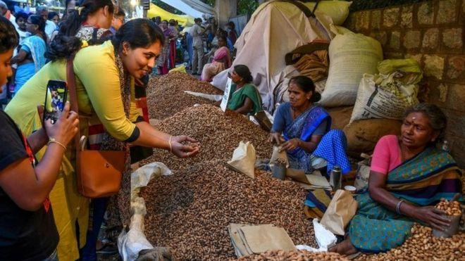 Mulher compra amendoim em feira livre na Índia