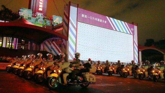 """今年的雙十節慶祝活動將在台北的總統府前舉行,但是觀禮台旁的大屏幕沒有""""中華民國""""四個字引起藍營的不滿。"""