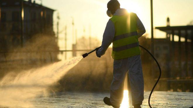 عامل في مجال الصحة يرش المياه