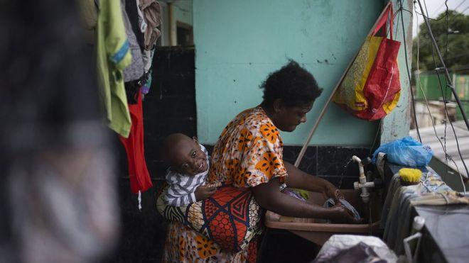 Congolesa lavando roupa no tanque após chegar do trabalho, enquanto carrega o peso de seu filho nas costas