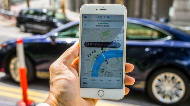 Mão segura celular com o aplicativo Uber na tela, visto de dentro de um carro