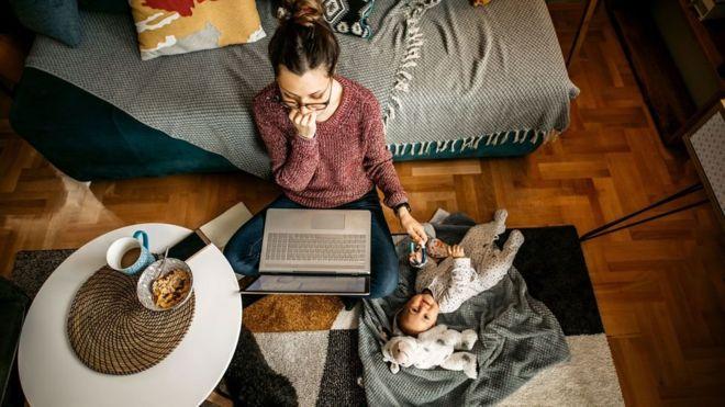 Una mujer frente una computadora portátil trabajando y atendiendo a su bebé a la vez