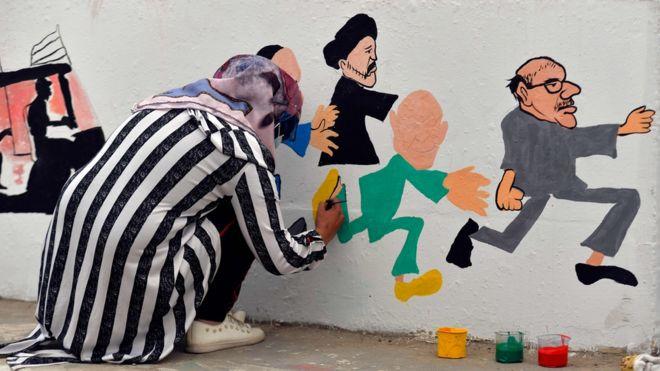 فتاة ترسم جدارية في بغداد