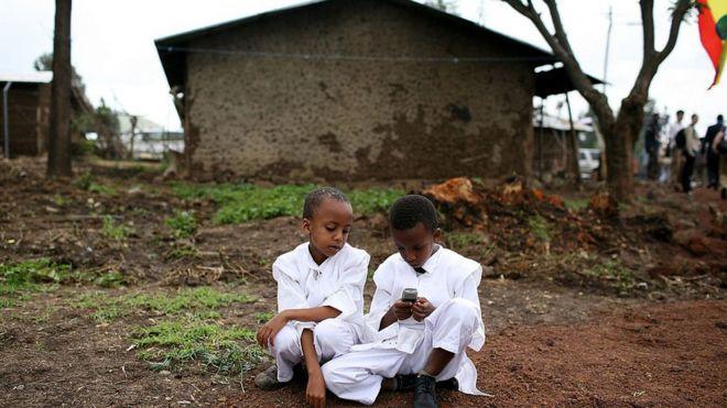 Niños etíopes jugando con un celular