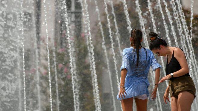 Dos mujeres refrescándose con chorros de agua de una fuente