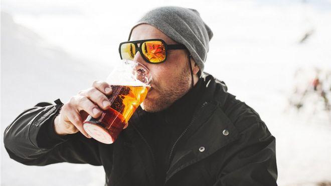 Hombre bebiendo cerveza en la nieve