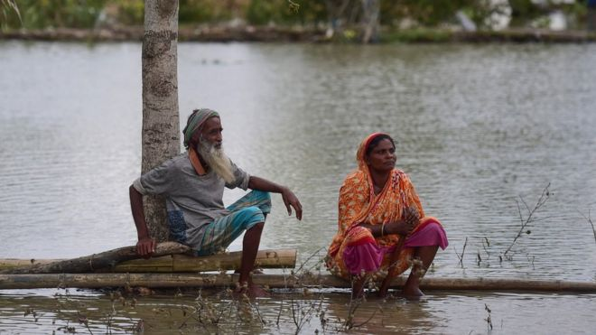 A marooned couple sit on a log close to their home, surrounded by flood water following the cyclone on May 4