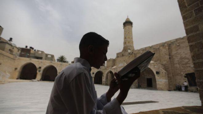شاب فلسطيني يتلوا آيات القرآن الكريم في مسجد العمري الكبير في مدينة غزة