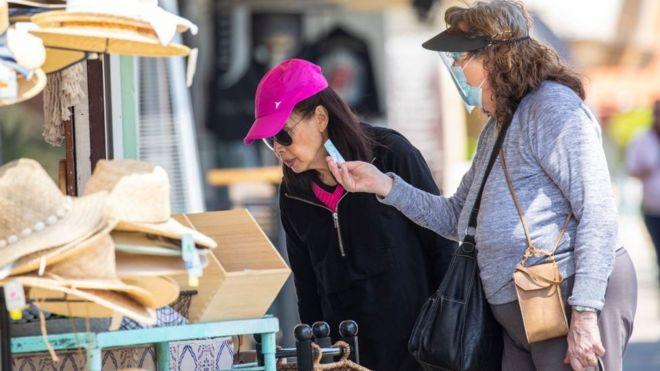 Uma mulher com máscara, e outra sem, olhando produtos na área externa de uma loja