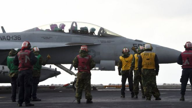 US Navy crew members stand by an EA-18G Growler electronic warfare aircraft on the deck of the Nimitz-class aircraft carrier USS Carl Vinson during a South Korea-US joint military exercise in seas east of the Korean Peninsula on 14 March 2017