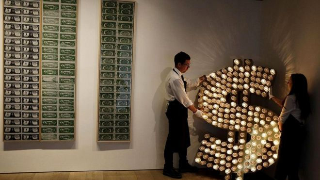 Знак доллара до сих пор пользуется популярностью у художников (Тим Ноубл и Сью Уэбстер устанавливают свою сияющую инсталяцию рядом с работами Энди Уорхола)