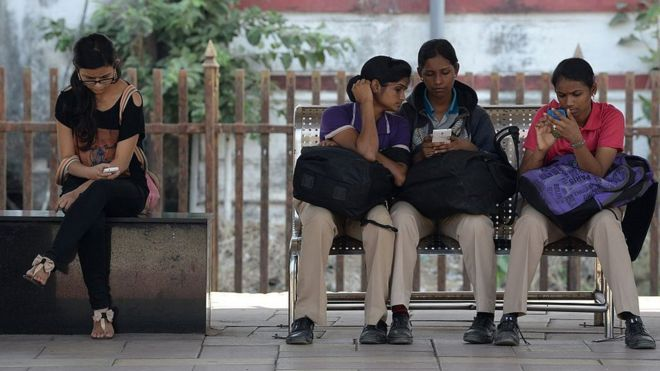 Indian women check their mobile phones at a free Wi-Fi zone in Mumbai in February 2016