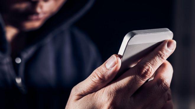 Persona con capucha sosteniendo un teléfono.