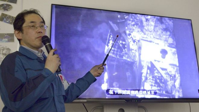 Image result for Tepco officials showed images of remote-controlled equipment lifting the fuel rods photos