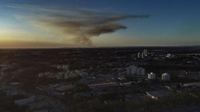 Vista aérea de Cuiabá, com alguns prédios se destacando, e fumaça ao fundo